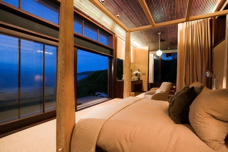 Bedroom of a luxury beach cottage with picture windows facing the sea.